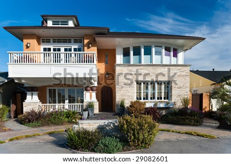 A very large house squeezed between two small houses. - stock photo