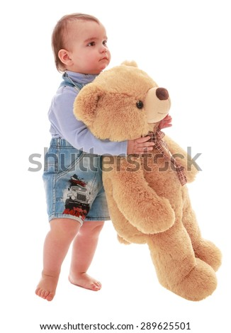A very little boy carries a Teddy bear - isolated on white background - stock photo