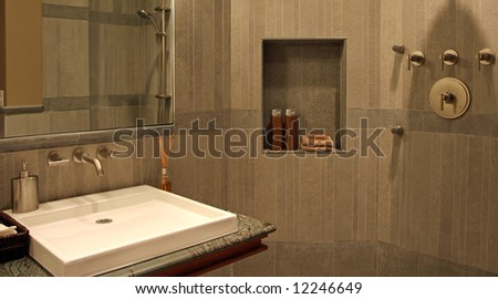 A very modern bathroom with stone walls and a flat sink. - stock photo