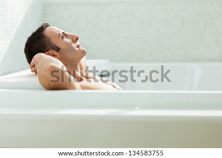 a very muscular and fit man relaxing in a luxury bathtub - stock photo