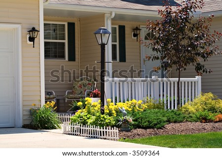 A very neat small home or condo with a white fence. - stock photo