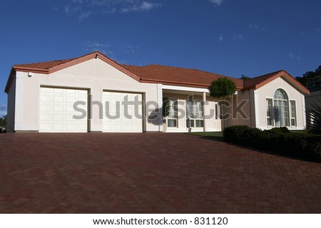 A very nicely presented cream single storey house - stock photo