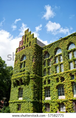 A very old and grand ivy covered building on the campus grounds of Lund university in Sweden. - stock photo