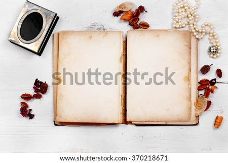 A very old book with stained pages is open, providing copy space, laying on a white washed, rustic wooden table. Flat lay perspective with horizontal composition. Feminine items surround the book - stock photo