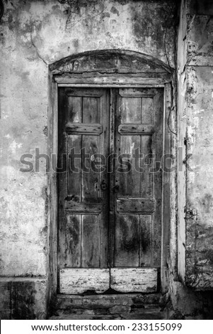 A very old door of a building in black and white vintage tones. - stock photo