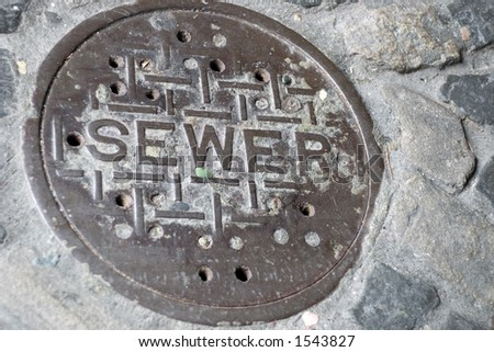 A very old sewer manhole cover set in cobblestone - stock photo