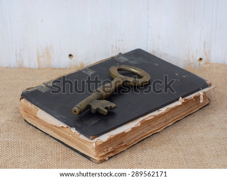 A very old, worn book laying on burlap in front of a rustic wooden wall. Concept of knowledge being the key to success or ancient mysteries are contained inside. Copy space above book. - stock photo