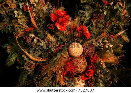 a very ornate and gorgeous christmas wreath isolated on black background with mood lighting and shallow DOF - stock photo