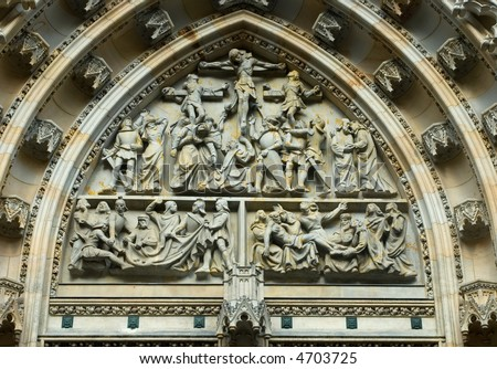 A very ornate carving above the entrance to the Prague Castle Cathedral. - stock photo