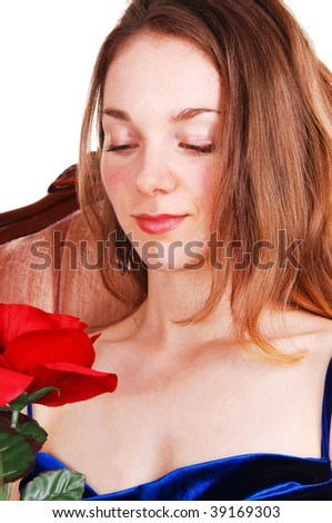 A very pretty young girl in an royal blue dress and gorgeous long red hair sitting in a pink armchair, holding a red rose to her face, on white background.