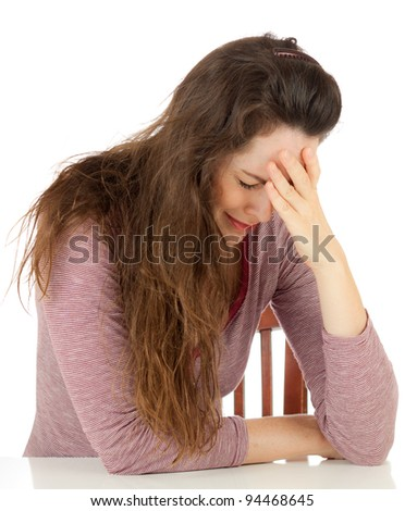 A very sad and depressed woman sitting at a table crying. Isolated over white.