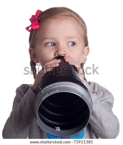 A very serious young child is talking secretly into her pretend microphone.  She is keeping an eye on someone so they do not see her. - stock photo
