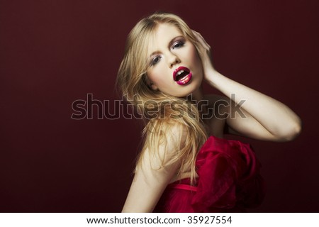 a very sexy blond girl on red background - stock photo