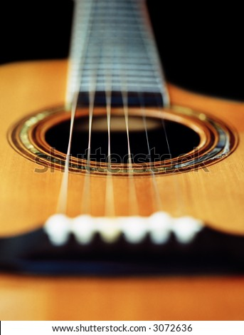 A very short depth-of-field image of an acoustic guitar from the bridge looking up the neck. - stock photo