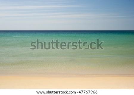 A very simple view of a calm tropical ocean horizon with sand beach and blue sky. Phuket, Thailand. - stock photo