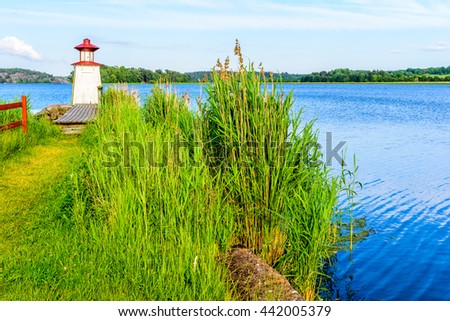 A very small lighthouse at the inlet of Gota canal in Mem, Sweden. - stock photo