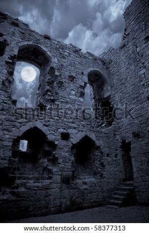 A very spooky castle in the moonlight, the moon is shining through a window.