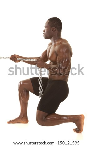 A very strong man is pulling on a metal chain. - stock photo