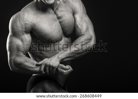 A very strong man on a dark background. Male bodybuilder.
