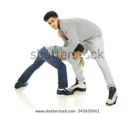 A very tall teenage man wrestling with his elementary brother.  On a white background. - stock photo