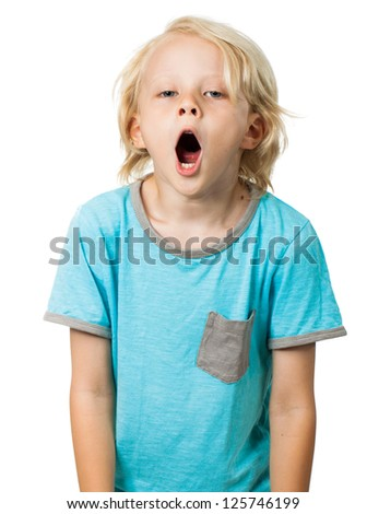 A very tired and bored young boy yawning and looking at camera. Isolated on white. - stock photo