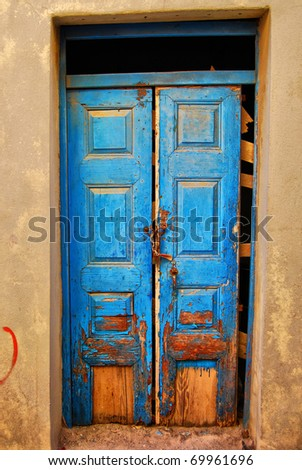A very worn and battered old blue door locked with a rusty chain situated on the Greek isle of Crete. - stock photo