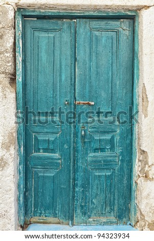 A very worn and battered old blue door situated on the Greek isle of Santorini. - stock photo