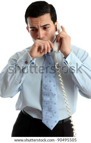 A very worried or anxious businessman or other professional on the phone.  White background. - stock photo