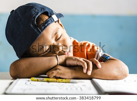 a very young boy student in the school sleeping on his book. Thai school in a small village