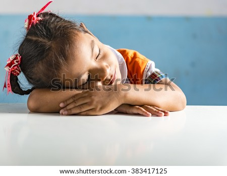 a very young girl student in the school sleeping on the table. Thai school in a small village