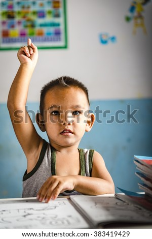 a very young student boy has a question for the teacher. Thai school in a small village - stock photo