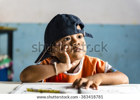 a very young student boy on dreaming at school. Thai school in a small village - stock photo