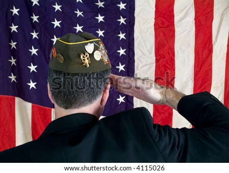 A Veteran wearing a decorated cap, saluting the American Flag. - stock photo