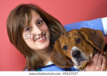 A veterinarian holding a beagle dog isolated over a red background. - stock photo