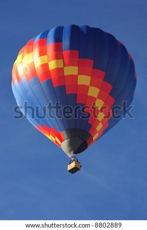 A vibrant hot air balloon high in the sky. - stock photo