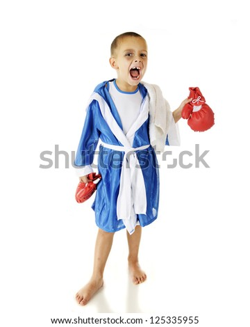 A vicious-looking preschooler holding his boxing gloves as he looks at the viewer in his robe.  On a white background. - stock photo