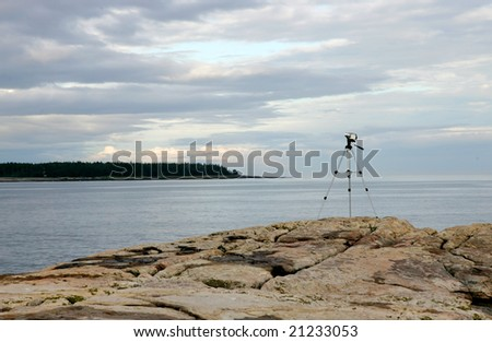 a videocamera on a tripod overlooking the water - stock photo