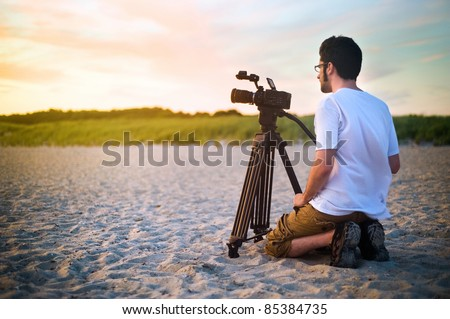 A videographer documenting a sunset on the beach. - stock photo