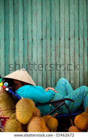 A Vietnamese fruit vendor selling the tropical fruit, durian, takes an afternoon nap and under the popular conical hat - stock photo