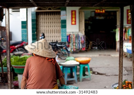 A Vietnamese market vendor donning the popular conical straw hat waits for customers by the road side