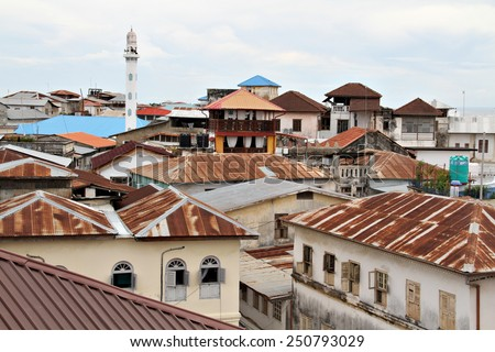A view across the rusted corrugated iron roofs of Stone Town in Zanzibar, Tanzania. - stock photo