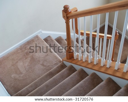 A view down a stairway in a modern american home. Carpeted stairs and a wooden banister and railing are visible - stock photo