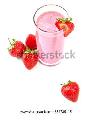 A view from above on blended strawberries squeezed in a smoothie. A transparent glass of a sweet shake isolated on a white background. Delicious and ripe strawberries and an organic yogurt.