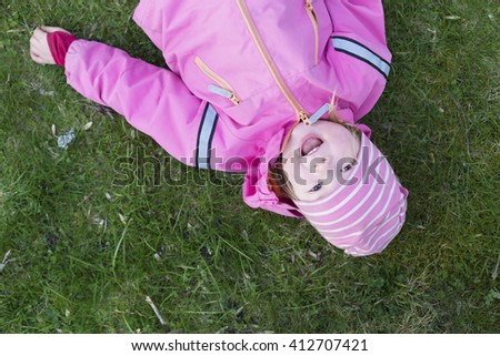 a view from above portrait of happy smiling small cute girl laying on the bright green grass  - stock photo