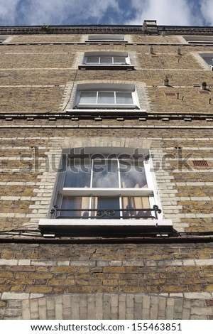 A view from below of a column of sash windows - stock photo