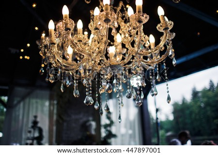 A view from below on a rich chandelier hanging from a ceiling - stock photo