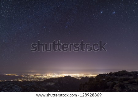 A view from midway up Mount Lemmon, looking down into Tucson, Arizona.  Orion, Jupiter, and the Pleiades float above the city lights.