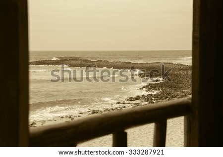 A view from the wooden terrace through the opened window on ocean beach. Algarve, Portugal. Selective focus on the landscape. Aged photo. Sepia. - stock photo