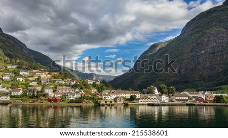 A view in the sunset light over little town of Aurland Norway as seen from the deck of the ferry cruising on the spectacular Naeroyfjord between Flam and Gudvangen - stock photo