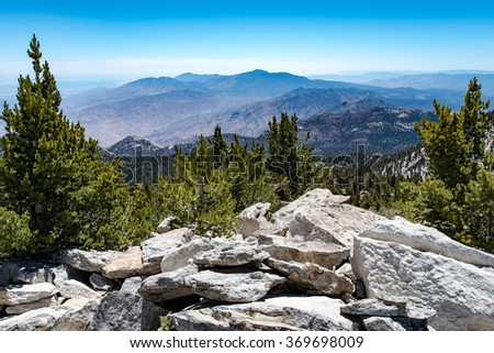 A view looking down from the top of a mountain range. Below you can see the lower mountain peaks and the forrest. - stock photo